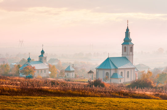 catholic and orthodox churches at foggy sunrise. lovely countryside scenery in autumn. creative toning
