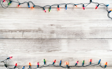 Wall Mural - Christmas lights bulb decoration on white wood plank. Merry Christmas and New Year holiday background. vintage color tone.