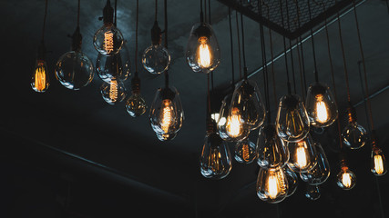 Wall Mural - Beautiful vintage luxury light bulb hanging decor glowing in dark. Retro filter effect style.