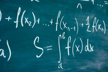 Mathematics function integra formulas written by chalk on the chalkboard.