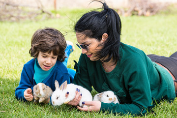 Mom and son holding small rabbits in garden