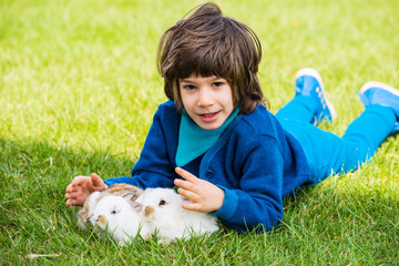 Boy laying on grass with bunnys
