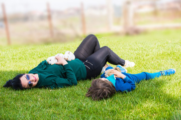 Mother and son laying on grass with bunnys