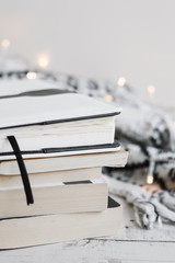 Pile of books, lights for home decoration and knitted blanket on wooden background