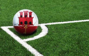 soccer ball on a green field, flag of Gibraltar