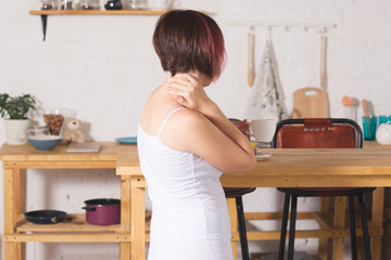 Neck pain, woman suffering from backache at home