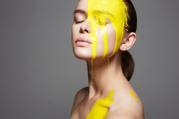 Young woman in Yellow paint. liquid paint flow