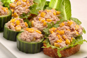 Toast and cucumber appetizers with tuna paste and corn
