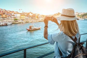Obraz Happy blonde woman - tourist shot on her smartphone camera in Porto Portugal - fototapety do salonu