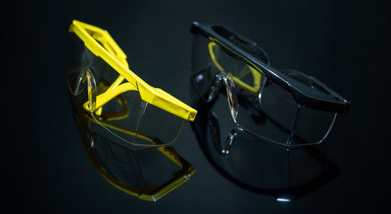 Close up view and low light. Protection glasses on black glass floor. There is reflection.