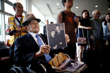 A man who has been selected as a participant for a reunion holds an old picture at a hotel used as a waiting place in Sokcho