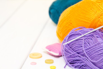 Colored threads for knitting on a white wooden background