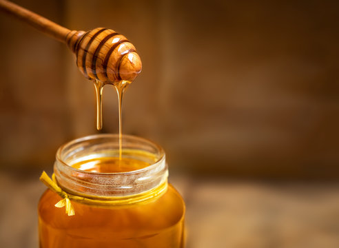 Honey in a glass jar with honey dipper on rustic wooden table background. Copy space.