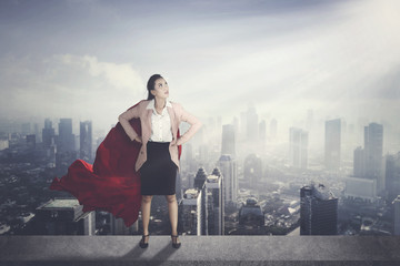 Asian businesswoman with red cape against modern city background