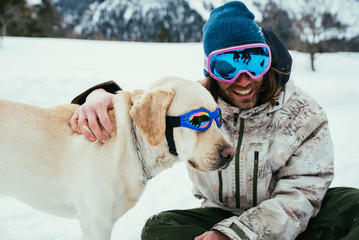 Friends playing with dog on the mountains, on th snowy ground