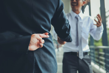 Trickery Concept.Business partners shaking hands with one of them holding fingers crossed behind back.