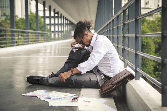 Unemployment concept , businessman unemployed from company sit on the overpass.Young business man stressed.Effect from coronavirus