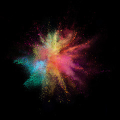 Explosion of coloured powder isolated on black background.