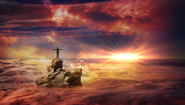 A man with spread arms standing on a rock protruding above the clouds and looking at a flare on the horizon.