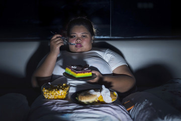 Overweight woman eating junk food in bed before sleeping