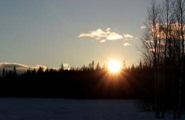 midnight sun over frozen lake in lapland, finland