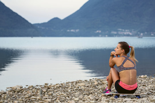Girl sitting and looking at a lake