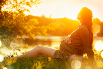 Pregnant woman sitting on green grass in summer park, enjoying nature. Healthy pregnancy concept