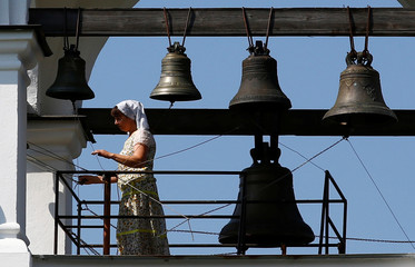 "A woman rings bells at an Orthodox church, during the ""Yablochniy Spas"", or Apple the Saviour, a religious holiday in Minsk"