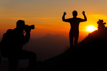 Mountain photographer is a girl with sunset yoga position in silhouettes