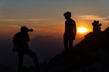 Photographer performs photography to a girl at sunset in high mountains in silhouettes
