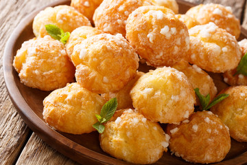Chouquettes French Cream Puffs dessert is decorated with pearl sugar and mint closeup. Horizontal