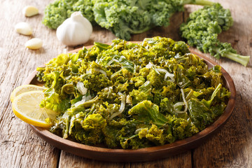 Portion kale of leaf cabbage cooked with onions, garlic, oil and lemon close-up on a wooden background. horizontal