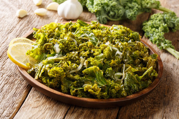 Kale or leaf cabbage cooked with onions, garlic, olive oil and lemon close-up on a plate. horizontal