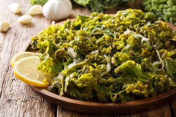 Healthy diet foods: kale, onion and garlic and lemon close-up on a plate. horizontal