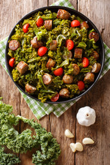 kale with grilled sausages, fresh tomatoes and garlic close-up on a table. Vertical top view