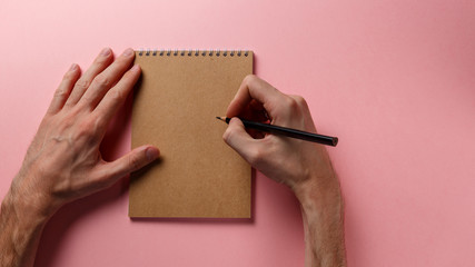 Man's hands holding pencil and spiral notepad as mockup for your design. Pink background. Top view. Flat lay. Pastel background. Back to school and education concept