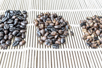 Roasted coffee beans of three different level in black bow on grunge wooden background,Coffee bean 3 level roast
