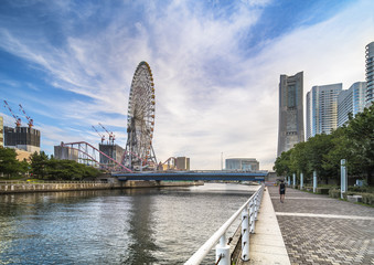 Big Wheel at Cosmo World Theme Park in the Minato Mirai district of Yokohama with the Landmark Tower and the Kokusai bridge and a river dock where pedestrians make their jogging.