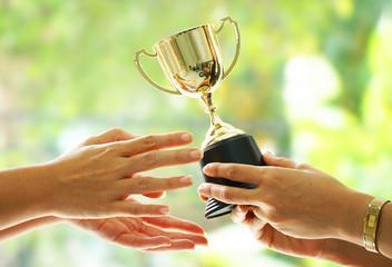 Winner receive trophy on blur green background.