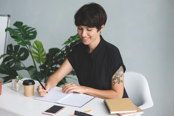 Businesswoman sitting at desk and makes a note