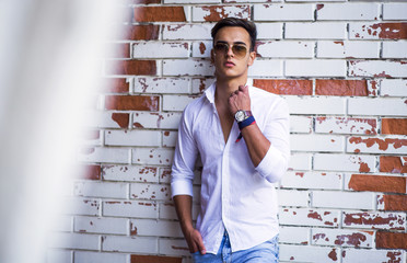Young stylish man model in classic clothes posing near the brick wall