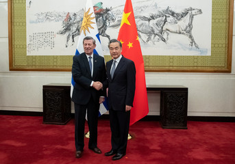 Chinese Foreign Minister Wang Yi shakes hands with Uruguay's Foreign Minister Rodolfo Nin Novoa, at Diaoyutai State Guesthouse in Beijing
