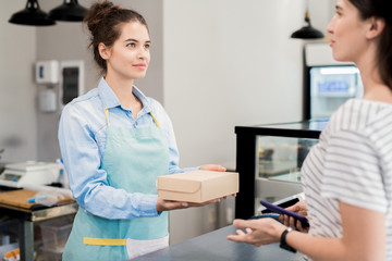 Waist up portrait of modern young woman holding box with takeaway food and giving it to customer while working behind counter in small bakery