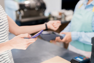 Close up of unrecognizable woman paying via NFC smartphone in local shop, copy space