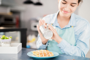 Portrait of smiling young woman pouring cinnamon and powdered sugar over fresh waffles while preparing order in small cafe, copy space