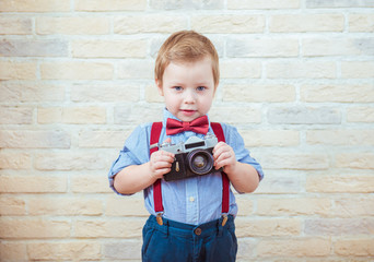 Cute little boy standing with retro camera on brick wall background