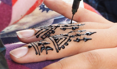Henna tattoos being put on hands in Morocco
