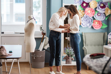 Two smart-looking pretty women wearing white shirts are standing in front of the mirror and measuring each other. Fashion, tailor's workshop.