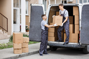 Two young handsome movers wearing uniforms are unloading the van