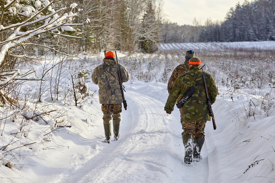 group of hunters in winter forest with carbines and shotgun